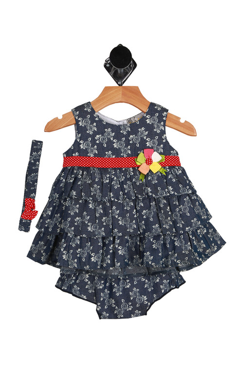 Front shows denim material with white flower pattern all over, red and white polkadot band at chest with matching bloomers and headband.