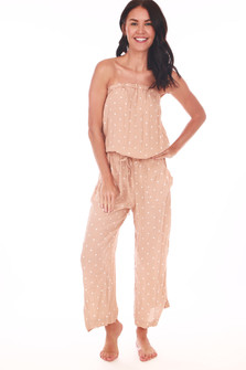 full body front shows billowing strapless top with elastic waistband and waist tie, side pockets and ankle length pants. jumpsuit is in a blush and white polka dot pattern.