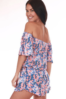 back shows off the shoulder sleeves with all over blue and white flowers on salmon pink background. Shorts feature ruffle at hemline