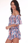 side shows off the shoulder sleeves with all over blue and white flowers on salmon pink background. Shorts feature ruffle at hemline