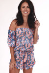 front shows off the shoulder sleeves with all over blue and white flowers on salmon pink background. Shorts feature ruffle at hemline