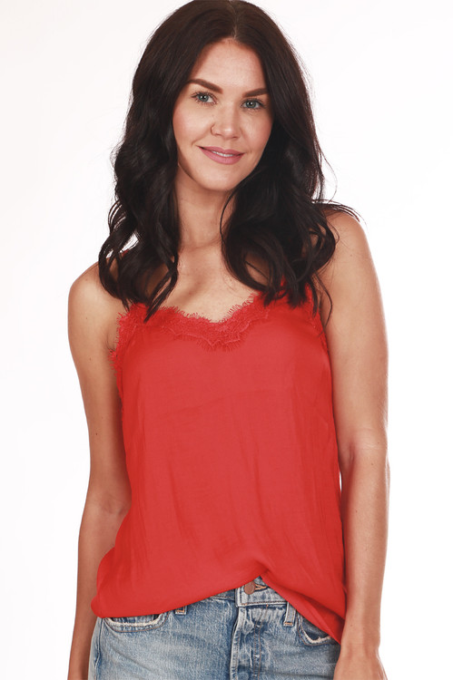 front shows bright red spaghetti strap blouse with lace hemline and satin material. Shown paired with light blue jeans.