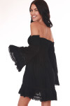 Back shows black mini dress length featuring a smocked top with off the shoulder bell sleeves tub top style top, and crochet lace detailing at hemlines.