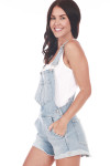 Side shows Light blue denim overall shorts. Shown paired with white short sleeve tank.