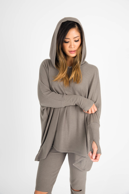 front shows hood on model with thumbholes at bottom arm length and oversized fit in grey/green color.
