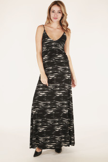 full body front shows dress with drop waist in black and tan stripe-like pattern with spaghetti straps.
