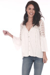 Front shows off white long sleeve crochet blouse with crochet design on shoulders  and  v shape neck line shown paired with light   blue jeans..