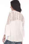 Back shows off white long sleeve crochet blouse with crochet design on shoulders and top of back.