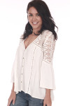 Side shows off white long sleeve crochet blouse with crochet design on shoulders  and  v shape neck line.