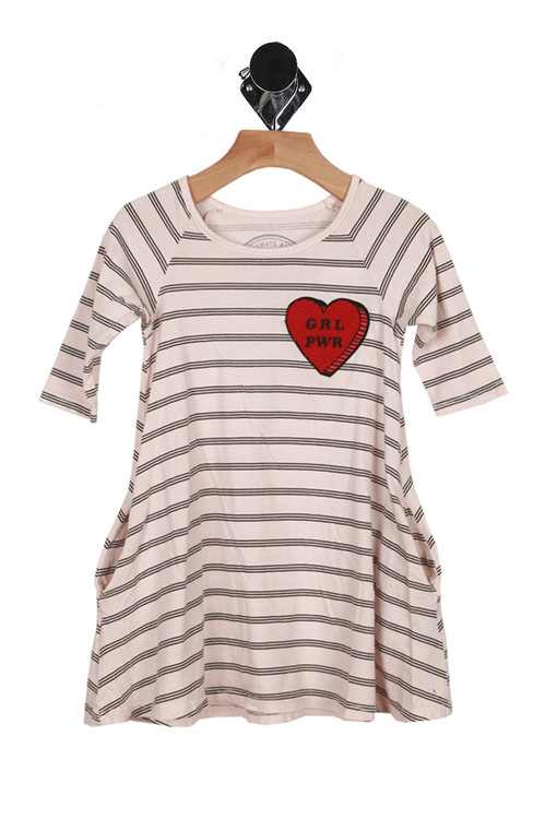 front of dress has scoop neck line with long sleeves, swing dress fit. Pattern has light pink background with black horizontal stripes.  Girl Power patch is a red heart