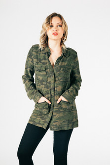 front of jacket shows models hands in front pockets & jacket has snap closure at front, long sleeves and all over green camo material