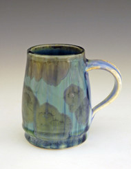 "This Java Mug is handmade by Bill Campbell based in Cambridge Springs, PA. The mug is 4 1/2"" x 5"" wide and holds 12oz it is shown in his cream/green/blue glaze. We offer two different Stellar glazes Cream/Green/Blue and Stellar New glaze, Light and Dark. All of his porcelain is functional; microwave, oven, dishwasher safe."