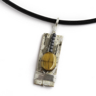 "TEN2 Sienna Hematite and Tiger Eye Necklace by Tessoro Jewelry, natural birchbark, hematite and tiger eye, sterling silver wrap, black leather cord 17"", pendant is 1 1/2"" x 1/2""."