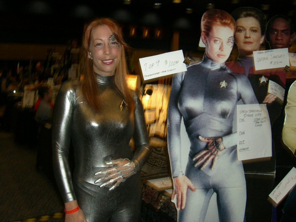 """Customer photo! Holly in her 7 of Nine (Star Trek) Costume. Back zipper (smooth front) Custom Catsuit by Suzi Fox shown in Gunmetal metallic foil coated Nylon Spandex. Customer used bungie cords for the ribbing. You can order this Catsuit in almost any fabric on this site.  • Available in gold, silver, copper, royal blue, purple, turquoise, red, green, fuchsia, gun metal, black faux leather/rubber Metallic foil coated spandex or any fabric on this site. • Your choice of front or back zipper (back zipper shown). • Optional 1 or 2-slider crotch zipper, and """"Selene"""" from Underworld TS Brass zipper, or aluminum circular slider zipper like Catwoman comic characters. • Optional wrist zippers • Optional ankle zippers • Optional finger loops • Made in the U.S.A."""