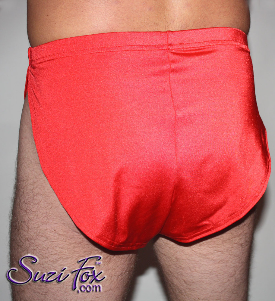 "Men's V front, Split Side Running/ Cover-Up Shorts shown in Red Milliskin Tricot Spandex, custom made by Suzi Fox. • Available in black, white, red, royal blue, sky blue, turquoise, purple, green, neon green, hunter green, neon pink, neon orange, athletic gold, lemon yellow, steel gray Miilliskin Tricot spandex, and any fabric on this site. • 1 inch no-roll elastic at the waist. • Front inside pouch. • The A15's are a ""V"" shape in the front, with less fabric on the front of the leg, and a very thin crotch. Commonly worn by runners and marathon participants, the A15's offer less chafing between the legs and does not inhibit the legs. • Made in the U.S.A."