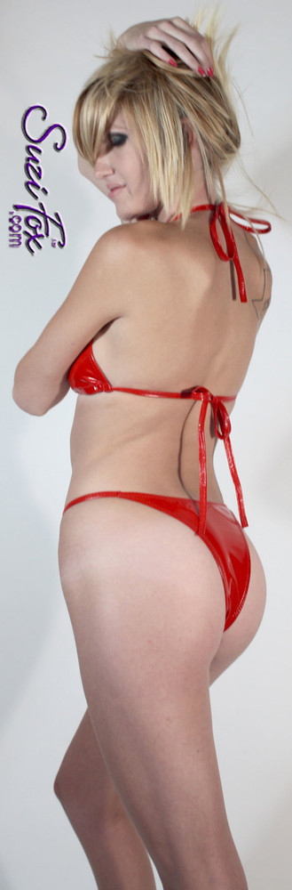 Womens skinny side Rio (1/2 rear coverage) Swim Suit bottom shown in Red Vinyl/PVC Spandex, custom made by Suzi Fox. • Custom made to your measurements. • Available in black, white, red, navy blue, royal blue, turquoise, purple, Neon Pink, fuchsia, light pink, matte black (no shine), matte white (no shine), black 3D Prism, red 3D Prism, Turquoise 3D Prism, Baby Blue 3D Prism, Hot Pink 3D Prism Vinyl/PVC, and any fabric on this site. • Top sold separately (shown with T1 string bikini top). • Made in the U.S.A.