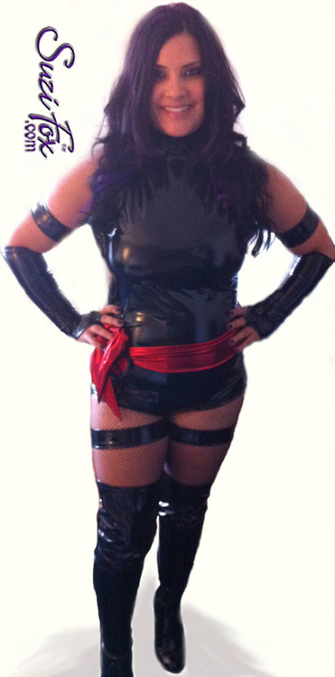 Custom Psylocke Costume shown in gloss Black Vinyl/PVC, custom made by Suzi Fox.  You can order this costume in almost any fabric on this site.  Costume includes 4 arm bands, 4 leg garters, bird finger gloves, red sash. • Available in gloss black, white, red, neon pink, light pink, fuchsia, purple, royal blue, navy blue, turquoise; matte (no shine) black, matte (no shine) white. This fabric is a 4-way stretch, vinyl/PVC coated spandex. • Optional Bust Cutout • Your choice of rears - French legs (Rio), Cheeky, Full, or Thong. • Made in the U.S.A.