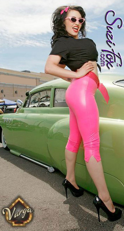 1950's Retro Pedal Pushers Leggings shown in Neon Pink Gloss vinyl/PVC, low rise, custom made by Suzi Fox.  Slit leg, shown in Capri length. You can order this in almost any fabric on this site.  • Custom made to your measurements! • Available in black, red, white, light pink, neon pink, fuchsia, purple, royal blue, navy blue, turquoise, black matte (no shine), white matte (no shine) stretch vinyl coated spandex. • 1 inch elastic at the waist. • Optional 1 or 2-slider crotch zipper. • Optional ankle zippers • Optional rear patch pockets • Optional belt loops • Made in the U.S.A.