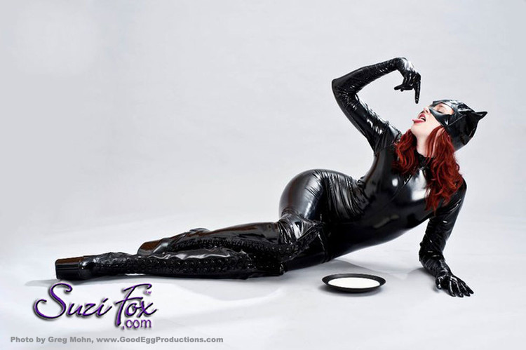 "Custom Catwoman Catsuit Costume by Suzi Fox shown in Black Gloss Black Vinyl/PVC coated Nylon Spandex.  Suggestion: use a latex paint pen to paint on the ""stitching"". You can order this Catsuit in almost any fabric on this site.  • Available in black, red, white, light pink, neon pink, fuchsia, purple, royal blue, navy blue, turquoise, black matte (no shine), white matte (no shine) stretch vinyl coated spandex. • Your choice of front or back zipper (front zipper shown). • Optional 1 or 2-slider crotch zipper. • Optional ""Selene"" from Underworld TS Brass zipper, or aluminum circular slider zipper like Catwoman comic characters. • Optional wrist zippers • Optional ankle zippers • Optional finger loops • Made in the U.S.A."