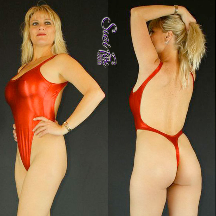 Womens One Piece T-back Thong Swim Suit shown in Red Metallic foil Spandex, custom made by Suzi Fox. • Custom made to your measurements. • The high leg hole, low back and t-back thong rear create a stunning and sexy suit. • Available in gold, silver, copper, gunmetal, turquoise, Royal blue, red, green, purple, fuchsia, black faux leather/rubber Metallic Foil, and any fabric on this site. • Made in the U.S.A.