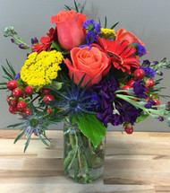 Fall hues with a mix of orange roses, yarrow, berries and thistle in a clear glass vase in Rockville MD, Palace Florists