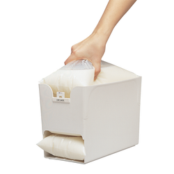 Holds up to 3 bags of 1.6L milk or juice. Dispenses them one at a time. Has a slot on front for expiry date tags.