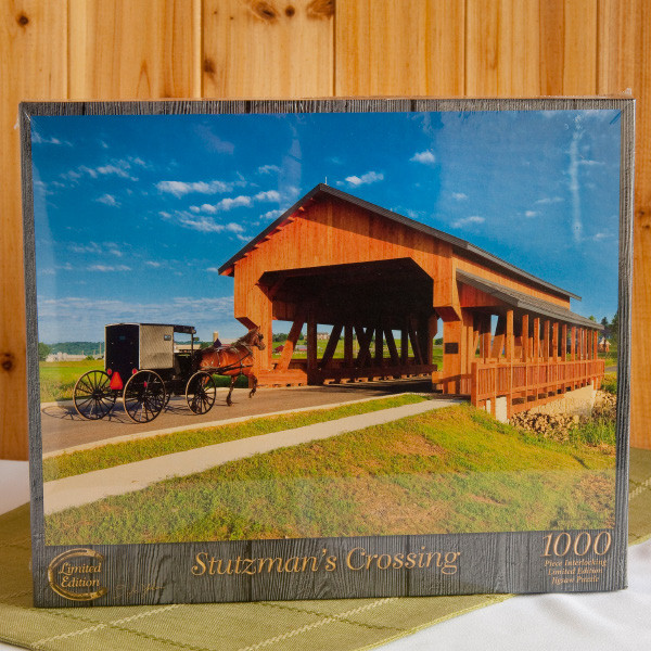 """Rejoice at the return of family time with this challenging 1,000-piece puzzle of the famous covered bridge in Walnut Creek, Ohio, named for the pioneer, Jonas Stutzman. Adults and children 12 and up will enjoy collaborating on their recreation of a gorgeous Doyle Yoder """"Saturday Morning"""" photo. The finished family masterpiece will measure 20 inch x 27 inch, an ideal size for framing."""