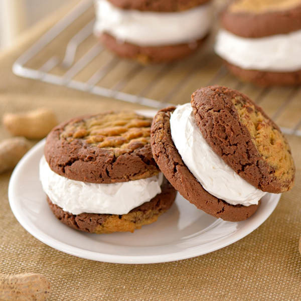 Chocolate Peanut Butter Swirl Cookies surround a layer of white fluffy vanilla filling.