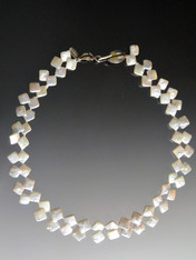 This one of a kind necklace looks like it's two strands but it's actually one strand of double square white pearls.  Never seen anything like it before or since.  A large sterling silver leaf clasp can be worn on the side or center. 17-1/2""