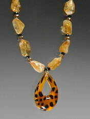 "Want some animal magnetism? This gorgeous strand of freeform citrine nuggets features Swarovski crystal stations, a limited edition Venetian glass golden leopard pendant, and a citrine sterling clasp. 19-1/2"" Pendant 2-1/4"" x 1-1/2"""