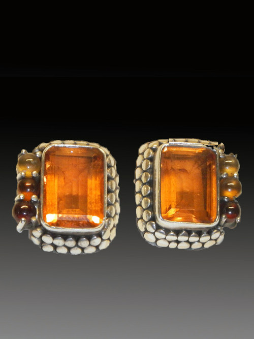 "These colorful vivid Amy Kahn Russell earrings feature a faeted whiskey quartz cabochons, set in an intricately patterned sterling silver dotted frame with citrine, tourmaline, and carnelian cabochons on one side. 1"" x 1/2"" Now posts; convert to clips for $15"