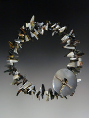 This dramatic versatile necklace features multi-toned black, white, gray and beige mother of pearl shards held with a large mother of pearl donut and sterling toggle.  Wear it super long or double for a dimenshional look.  34""