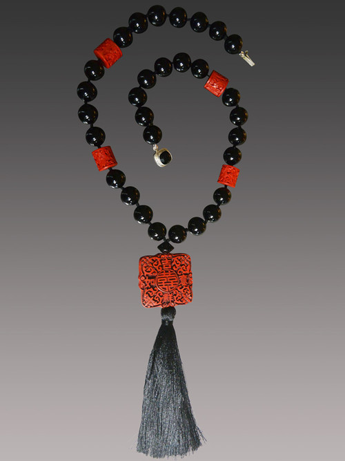 "This intricately patterned authentic hand-carved cinnabar square highlights a dramatic necklace featuring Venetian glass and barrel shaped complementary carved red cinnebar beads finished off with a luxurious black silk tassel. Totally elegant and very limited.  22"" Tassel 6.5"""