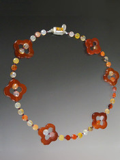 """This delightful necklace features rich carnelian quatrefoil stations, Hessionite garnet in colors from pale gold to rich brown with tiny faceted rhodolite garnet and an amber sterling clasp. Perfect to mix with other designs in the collection for an interesting layered look.  18"""""""