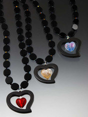 """A floating dichroic Venetian heart within a matte onyx freeform heart hangs from a chain of vintage jet beads. Choose Dichroic iridescent pale yellow, pale blue, or a 24K deep red heart topped with a pearl.. 21"""""""