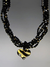 """Two opulent looks in one! Luxuriate in four strands of Grade AAA onyx dice specially ordered for this design randomly spaced with24K Swarovski crystals. A dramatic Venetian glass freeform gold and black tiger pattern heart suspended from a circle of onyx beads can be removed for an elegant torsade only look. ONLY TWO 18"""" (Longer lengths available on request)"""