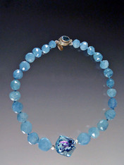 If you love aquamarine and want to make a statement, this is for you. Grade AAA rich blue grduated aquamarine faceted beads frame a beautiful Venetian Sasso window center with flashes of aqua, pink and black. A custom blue topaz clasp completes the picture. 18""