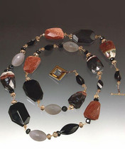 """A striking collage of shapes and colors! Faceted multi-agate slices artfully mixed with grey and black onyx, cognac Swarovski crystals, raw garnet, hand-wire non-tarnish gold/copper wire. Wear alone or pair with others in the collection. 34"""""""