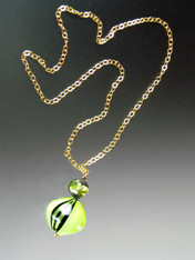 "This dramatic necklace features a a 2-1/2"" pendant glass beads on a 24K Ultraplate chain. The focal point is a 30 mm. peridot black Windows* blown Sasso Swirl topped with a 16mm matching lime round window where you can see an internal cylinder of 24K gold foil with an internal lime spiral and an end cap of deep dark chocolate. Chain is 24"""