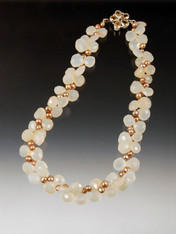 A collar of faceted pale yellow chalcedony plump teardrops spaced with luminous champagne freshwater pearls.  A custom sterling citrine flower clasp makes a charming center or side highlight.