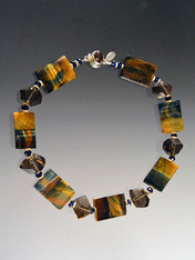 This dramatic necklace features blue tiger eye rectangles with flashes of blue, brown, and gold spaced with 14K rondels, Swarovski crystals and smoky topaz nuggets.