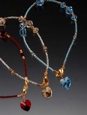 "A dazzling token of love says a lot but costs a little.   Rich red Swarovski crytals, 24K vermeil cast toggle clasp,and a dangling Swarovski heart charm!  A perfect gift for Valentine or anytime. 7""-7-1/2"" Choose red, London topaz blue, or light champagne."