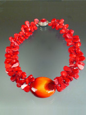 "If you want to make a WOW dramatic statement, this dazzling creation is for you.  Huge tomato red coral florets frame a one of a kind 2-1/2"" glazed Venetian Glass Disc (snagged at a trade show many years ago waiting for the right opportunity and setting) with a sunburst pattern of deep red, orange and gold . A red coral sterling 1"" custom clasp completes the design. Picture this on bright white, black, or the new bold tones of the season. Total length 22"""