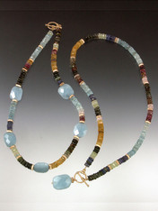 Yin and Yang - two stunning collars with different patterns but the same grade AA elements. The first features precious faceted tourmaline, citrine, and aquamarine and 14K fluted rondels with faceted aquamarine stations.  The second features an entire collar of the same precious gemstones and 14K rondels with a large faceted aquamarine dangle.  The limited edition swirl toggle clasp is solid cast 14K original price now!  ONLY ONE OF EACH!