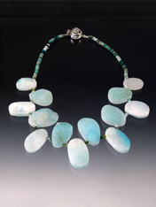 """Larimar is a rare gemstone found exclusively in a remote mountainous region of Santo Domingo. This unusual collar can be worn on the """"raw"""" side or as a flat polished collar. Multi-toned Peruvian Opal rondels and a custom moonstone clasp complete the piece   21"""""""