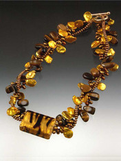 Be queen of the jungle with this dramatic, dimensional torsade featuring tiger eye, grade AAA gold and bronze petal pearls, and a magnificent 14K Venetian glass striped tiger highlight.  14K toggle clasp.  20""