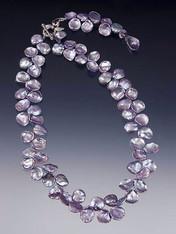 "A dimensional collar of absolutely huge purple/blue  petal pearls gathered in a custom amethyst sterling toggle clasp with a dramatic 3"" ""lariat"" dangle ending in a faceted lilac amethyst or iolite teardrop. Lariat looks smashing in the front or down the back of a low-cut dress."