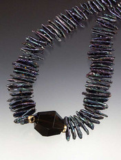 What could be more dramatic than intense dark blue biwa pearls with a rare Brazilian hammered onyx station surrounded by large 14K rondels, tiny sparkling Swarovski crystals and 14K clasp?  18""