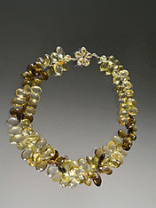 Many years ago I discovered this amazing strand of Grade AAA faceted gemstone quality multi-toned topaz briolettes shooting off sparks of lemon, olive, brown and other tones. I decided to kept this cluster together in a spectacular collar fit for a queen with a matching topaz silver custom clasp. 19""