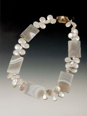 A striking collar featuring elaborately patternedgray agate slices spaced with silver pearls --super cool!